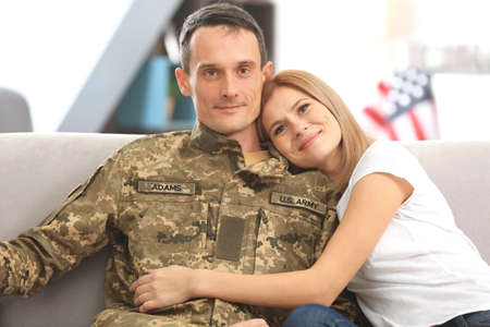 Happy soldier and his wife sitting on sofa at home Stock Photo