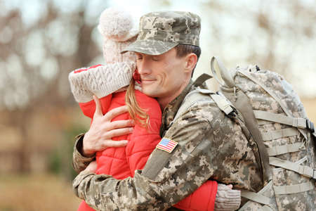 Soldier in camouflage hugging daughter outdoors Stock Photo