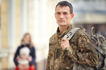 Soldier in camouflage outdoors with blurred family on background