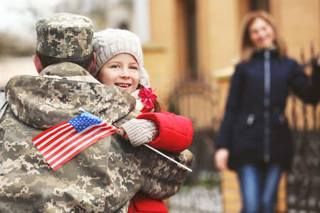 Happy reunion of soldier with family outdoors Stock Photo
