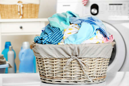 Clothes in wicker basket at laundry Imagens