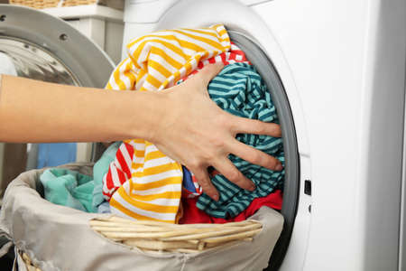 Female hands getting out clean clothes from washing machine 版權商用圖片