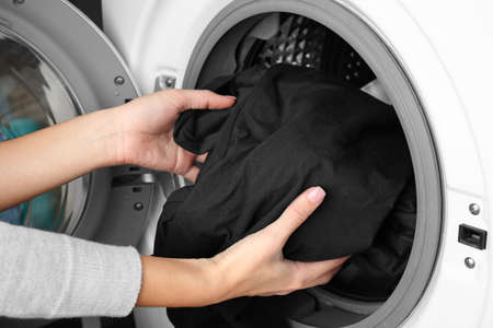 Female hands getting out clean clothes from washing machine Stock Photo