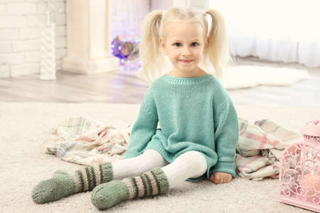 Cute little girl sitting on floor at home