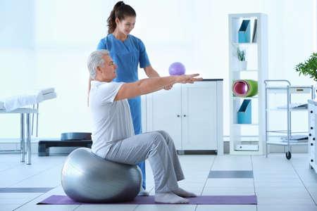 Fysiotherapeut die met patiënt in kliniek werkt