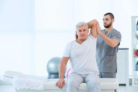 Fisioterapeuta trabajando con paciente en clínica