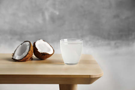 Glass of coconut milk and nuts on wooden table