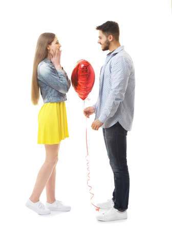 Young man giving balloon in shape of heart to his girlfriend, on white background Banco de Imagens