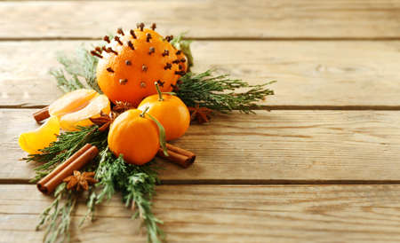 Composition of citruses, spices and coniferous branches on wooden background