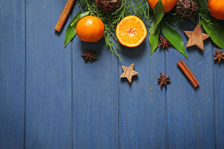 Composition of tangerine, spices and coniferous branches on wooden background