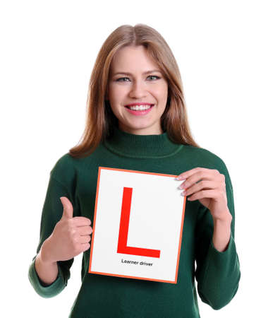 Young woman with learner driver sign on white background