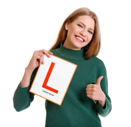 Young woman with learner driver sign on white background Stock Photo - 97861575