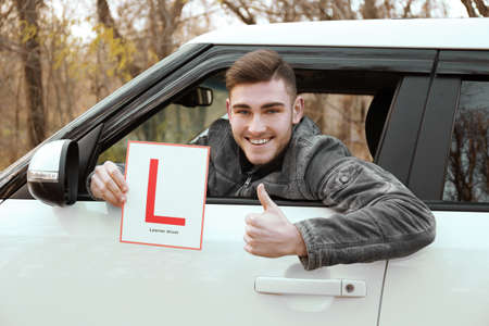 Young man holding learner driver sign while looking out of car window