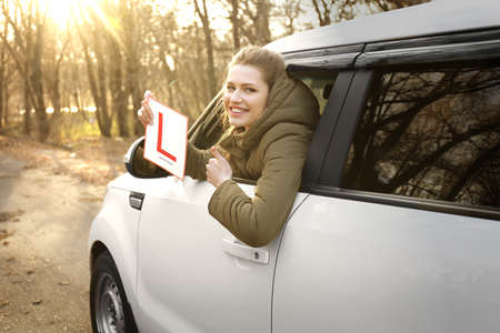 Young woman holding learner driver sign while looking out of car window Stock Photo