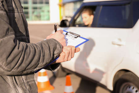 Instructor in driving school writing down results of exam, closeup