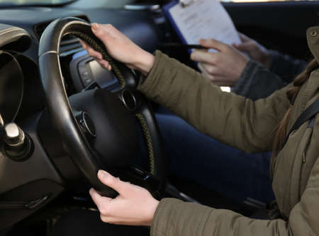 Young woman passing driving license exam while sitting in car with instructor