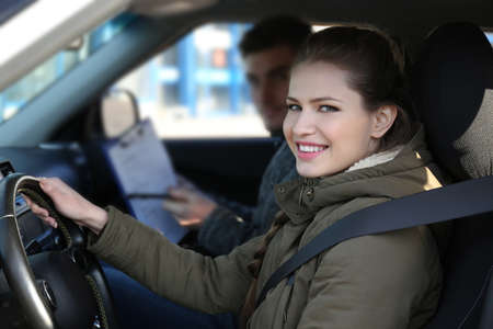 Young woman passing driving license exam while sitting in car with instructor Stock Photo