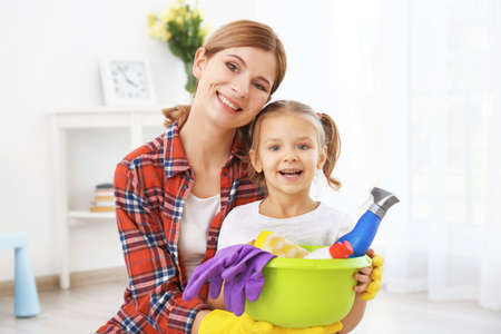 Little girl and her mother with cleaning supplies at home Stock Photo