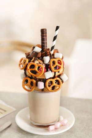 Milkshake, donuts and other sweets in glass on table