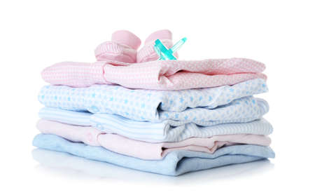 Baby shoes, pile of clothes and dummy on white background