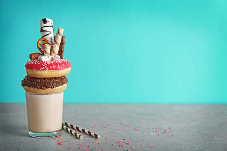 Milkshake, donuts and other sweets in glass on color background