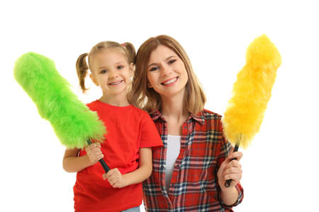 Little girl and her mother with dusters on white background