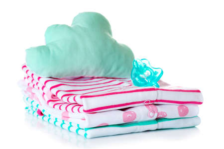Pile of baby clothes, cushion and dummy on white background Stock Photo