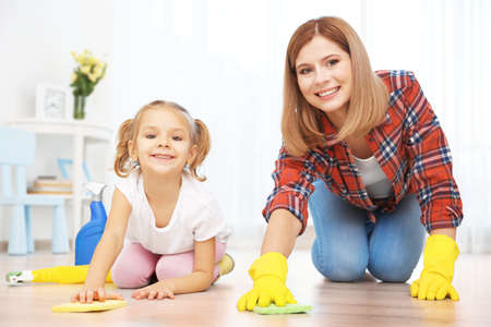 Little girl and her mother cleaning floor at home Stock Photo