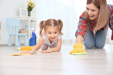 Little girl and her mother cleaning floor at home 免版税图像