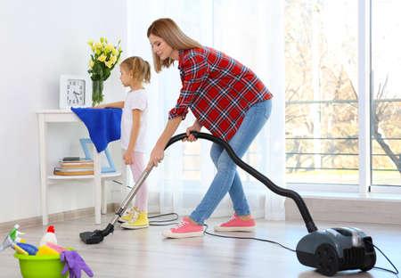自宅で掃除をする母と娘