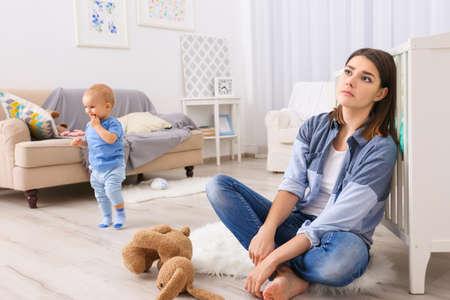 Przygnębiona młoda kobieta z uroczym dzieckiem w domu