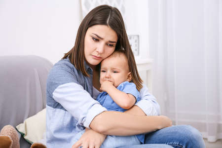 Deprimierte junge Frau mit nettem Baby zu Hause% 00