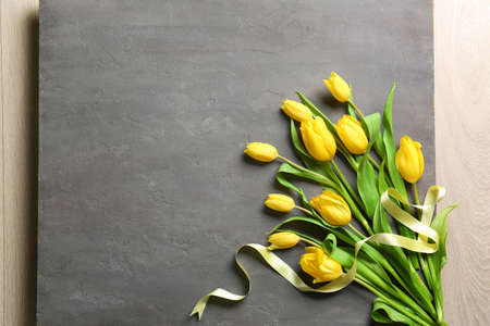 Yellow beautiful tulips with ribbon on gray background
