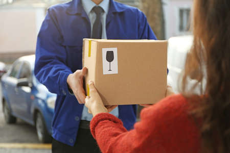 Courier giving parcel to customer, closeup
