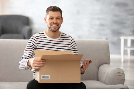 Handsome young man opening box with parcel while sitting on sofa at home