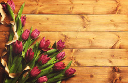 Pink beautiful tulips with ribbon on wooden background