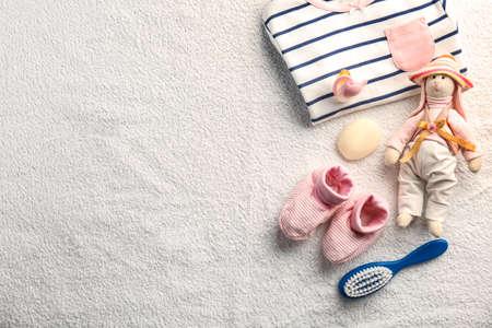 Babykleidung und Notwendigkeiten auf beige Tuchhintergrund% 00