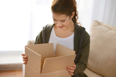 Beautiful young woman opening box with parcel at home Stock Photo
