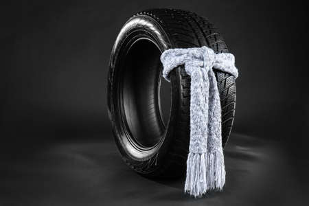 Rubber winter tire with warm scarf on dark background