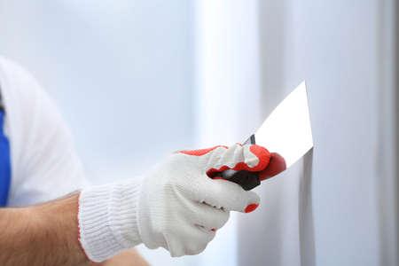 Hand of worker making repair in room