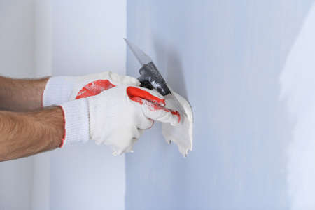 Builder using plastering tool for finishing wall Stock Photo