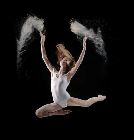 Little cute girl dancing with white powder on black background
