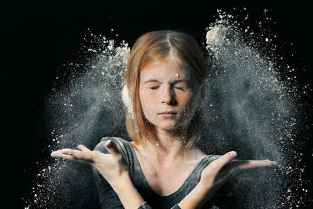 Little cute girl with white powder exploding around her on black background