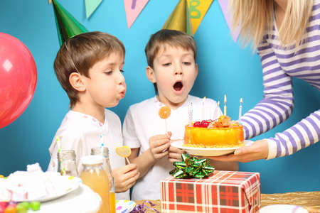 Cute little twins blowing out candles on birthday cake at party