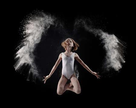 Little cute girl dancing with white powder on black background Standard-Bild - 97442756