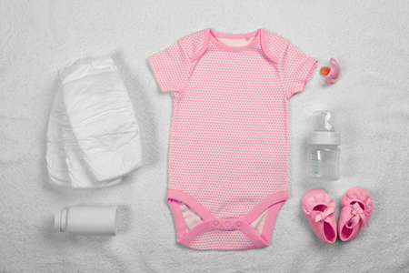 Baby care accessories and clothing on  fabric background Imagens