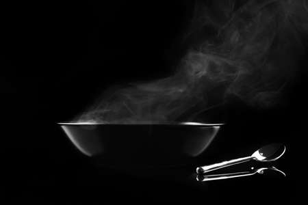 Steaming bowl on black background