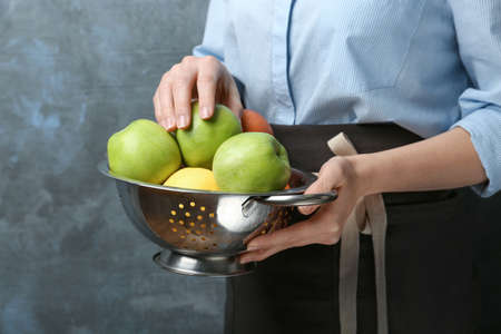 Young woman in apron holding colander with juicy apples, closeup Archivio Fotografico