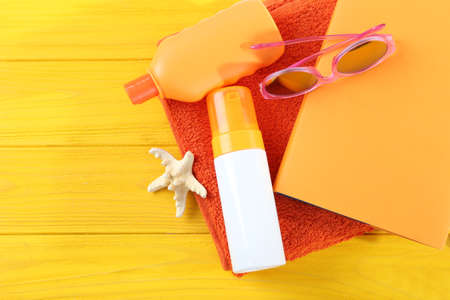 Vacation concept. Book and beach gear on yellow wooden table Stock Photo