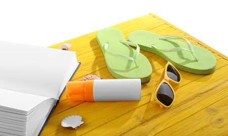 Vacation concept. Book and flip-flops on yellow wooden table